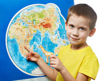 Little boy with toy giraffe shows Africa on world map Royalty Free Stock Photography