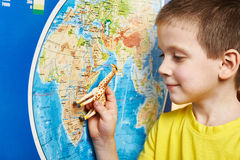 Little boy with toy giraffe shows Africa on world map Royalty Free Stock Image