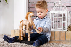 Little boy and toy horse. Little boy sits on a floor with toy horse Royalty Free Stock Photos