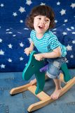 Little boy on a toy horse in a room. With blue sofa with stars stock image