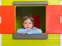 Little boy in toy house window Royalty Free Stock Image