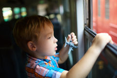Little boy with toy looking out of train window Royalty Free Stock Photos
