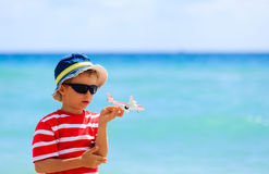 Little boy with toy plane at beach, travel concept Stock Images