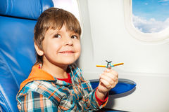 Little boy with toy plane fly in airplane Stock Image