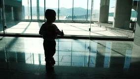 A little boy with a toy is walking around the airport in slow motion. A little boy with a toy is walking around the airport. His silhouette is visible. Action in stock video
