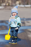 Little boy with a toy yellow shovel. Costs in a pool Royalty Free Stock Photos