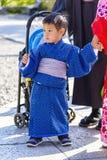 Little boy with traditional kimono in Kyoto, Japan. Kyoto, Japan - April 23, 2014: Little asian child with a blue kimono. The kimono is a traditional Japanese royalty free stock photos