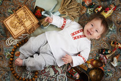 Little boy in a traditional russian shirt surrounded by russian antiques.  Stock Images