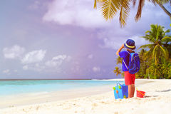 Little boy travel on beach with suitcase and Stock Image