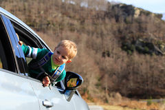 Little boy travel by car in autumn nature Stock Photo
