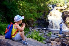Little boy traveler with backpack sits near falls Royalty Free Stock Photography