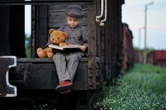 A little boy traveler is sitting on the wagon with a teddy bear and reading a book. stock photo