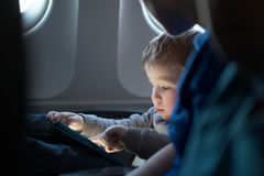 Little boy traveling in an airplane Stock Photos