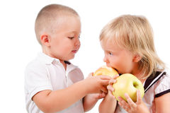 Little boy treating a girl with apples Stock Photos