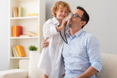 Little boy treating his father Stock Photos
