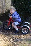 Little boy on tricycle. Little blond boy with hoodie sweatshirt on riding his tricycle outdoors stops to daydream royalty free stock image