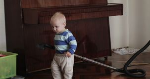 Little boy tries to clean room using vacuum cleaner. Funny blonde one year old boy helping mother stock video footage
