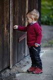 Little boy tries to open old door Royalty Free Stock Images