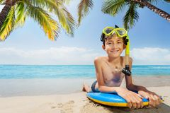 Boy in scuba mask lay under palm tree on surfboard Royalty Free Stock Image