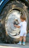 Little boy and truck wheel. Little boy near big truck wheel Royalty Free Stock Photo