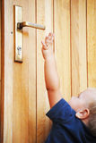 Little boy try to reach door handle Royalty Free Stock Images