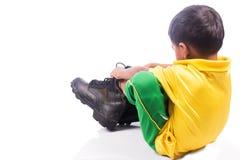 Little boy try wearing big shoe Stock Image
