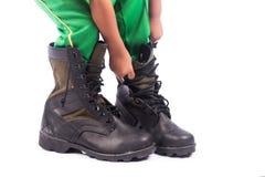 Little boy try wearing big shoe Royalty Free Stock Image