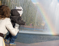 Little boy trying to reach the rainbow. In the park Royalty Free Stock Photo