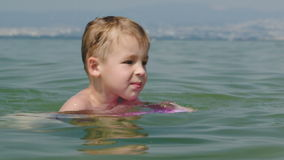 Little boy trying to swim on board in the sea stock video footage