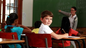 Little boy turning to smile at camera during class. In elementary school stock video footage