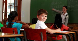 Little boy turning to smile at camera during class. In elementary school stock footage