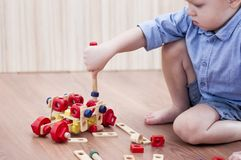 The little boy twists the bolt with a screwdriver. On floor. Kid plays with wooden eco constructor Stock Photo
