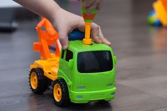 Little boy twists the bolt with a screwdriver. Kid plays with pl. Astick toy car Stock Image