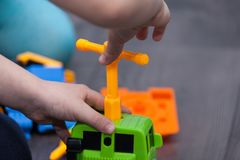 Little boy twists the bolt with a screwdriver. Kid plays with plastick toy. Little boy twists the bolt with a screwdriver. Kid plays with plastick toy car Royalty Free Stock Photography