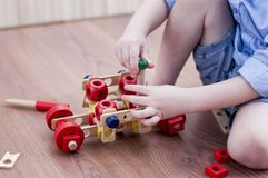 The little boy twists the bolt into a wooden machine. On floor in room Stock Image