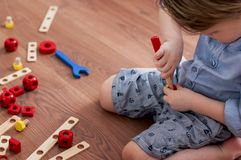 Little boy twists wooden screwdriver screw,. Sitting on the floor Royalty Free Stock Photos