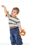Little boy with two bagels and pointing hand Royalty Free Stock Photography