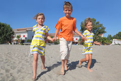 Little boy and two girls walking on beach Royalty Free Stock Photography