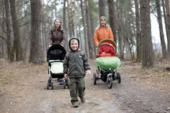 Little boy and two mums with carriages Royalty Free Stock Photography