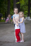 Little boy and two older cousins, meeting in the summer park stock photography