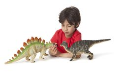 Little boy with two toy dinosaurs