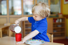 Little boy of two years having breakfast at nursery Stock Photography