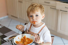 Little boy two years old eating pasta. Adorable little boy two years eating pasta indoor. Toddler child in domestic kitchen or in nursery. Cute kid and healthy Royalty Free Stock Photography