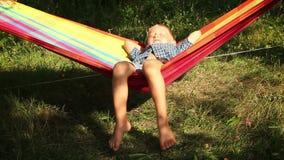 Little Boy tycker om varma solstrålar i hängmatta stock video