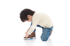 Little boy tying his shoes  in white. Little asian boy tying his shoes  in white background Stock Images
