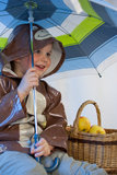 Little boy with umbrella and basket full of apples Royalty Free Stock Photo
