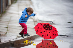 Little boy with umbrella, jumping in puddles Royalty Free Stock Images