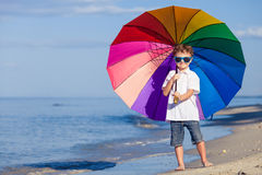 Little boy with umbrella standing on the beach Stock Photo