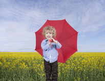 Little boy with umbrella in front of an oilseed field Royalty Free Stock Photography