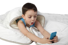 Little boy under blanket look astonished to smart phone Stock Photography